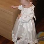Рассматривает бусинки на платье.