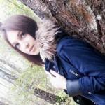 Прислонившись к дереву.
