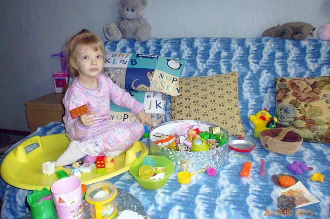 На диване с игрушками.